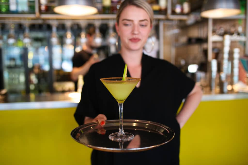A waitress with a cocktail on a tray