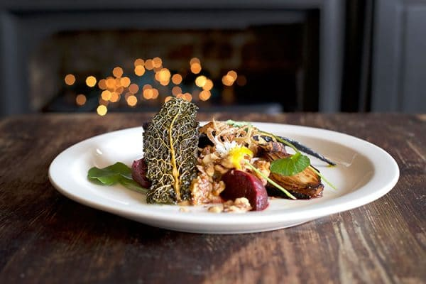 pubs with fires, colourful plate of vegetables and giant kale crisp in front of a fire, gluten free restaurants Brighton, food pubs Brighton