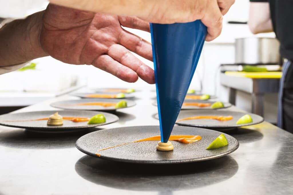 Close up of a piping bag finishing of a small plate