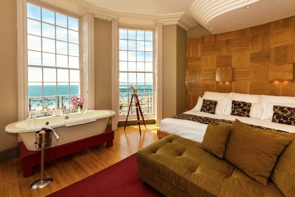 A hotel room with sea views, and a bathtub in the bay window iwth an ice bucket of Champagne