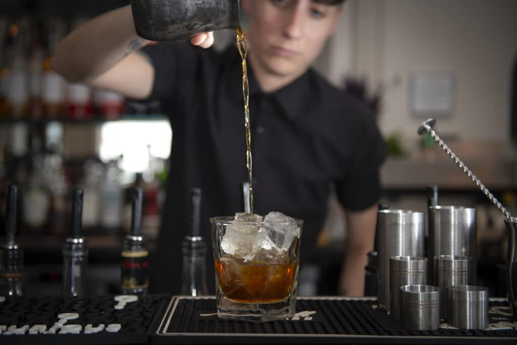 A mixologist in a blak shirt is at a granite bar mixing a cocktail