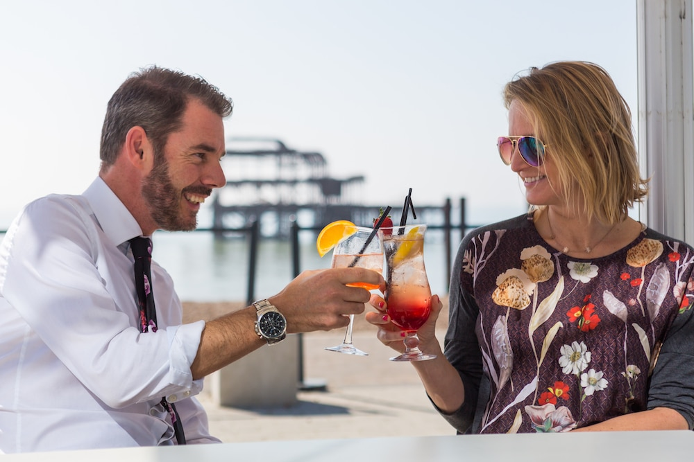 People enjoying cocktails on a sunny day on the terrace with the West Pier in the background.