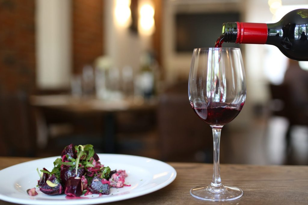 Best Restaurants in Sussex, wine being poured and a plate of food at Limes of Lindfield