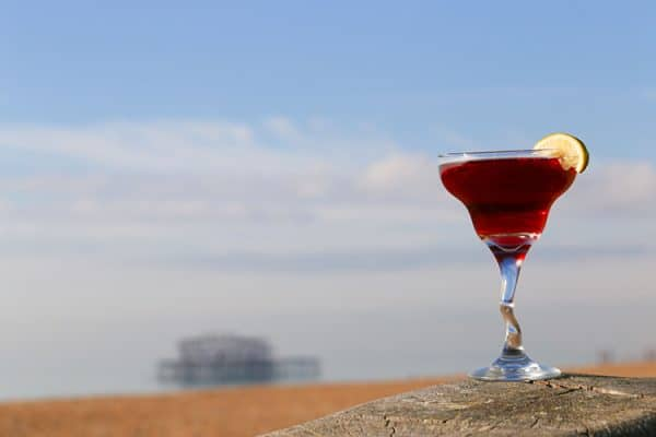 A bright red cocktail photographed on a wall with the beach in the background
