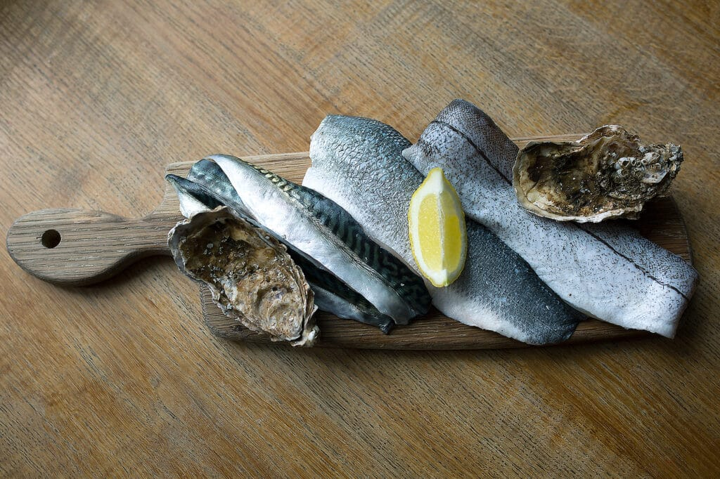 A wooden paddle with filleted fish and lemon