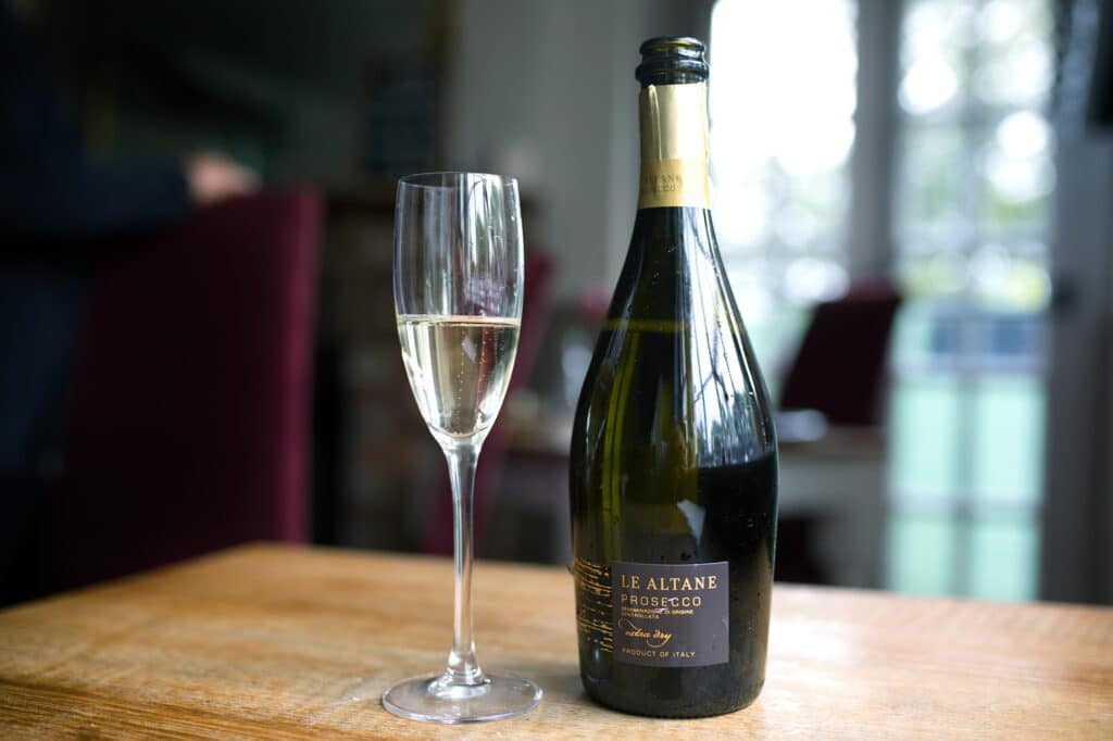 A bottle of sparkling wine and a glass on a wooden table, a large window looking out onto a garden is in the background.