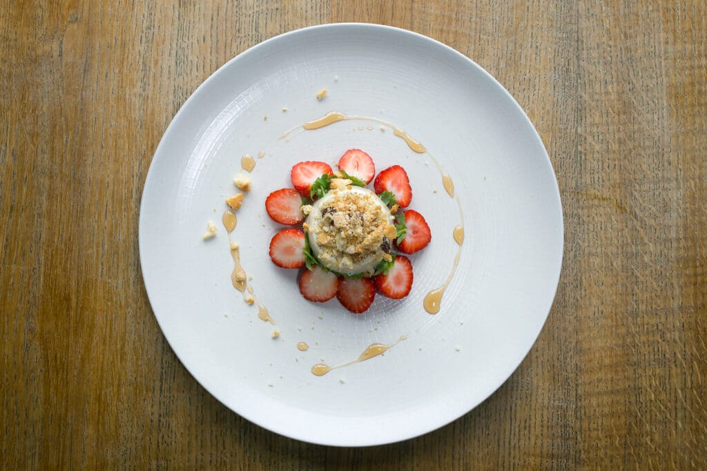 Overhead shot of a dessert on a white plate, a ring of strawberries about an individual cheesecake