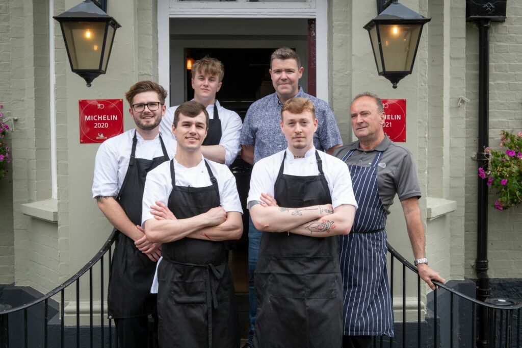 five chefs and owner taking group picture on the enterance of veneu