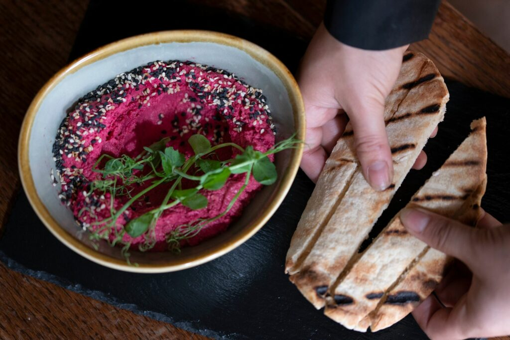 Beetroot infused hummus with blackened sesame seeds served with seared pitta bread. - Calamari fritti in a light peppery batter served with our black squid ink garlic mayonnaise