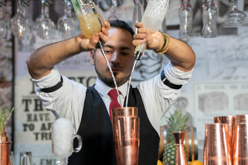 Bartender sipping alcohol in cocktail shaker