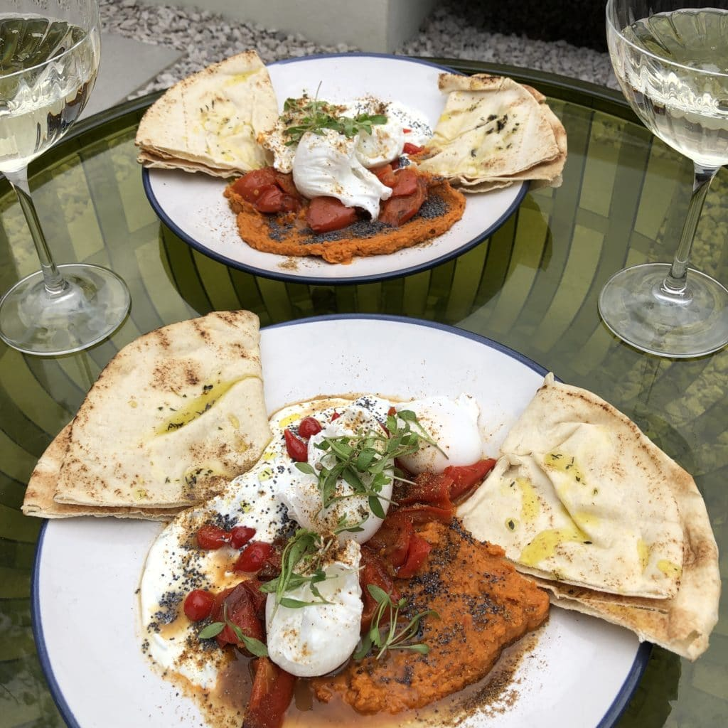 two plates of brunch laid out on a glass table with glasses of sparkling wine