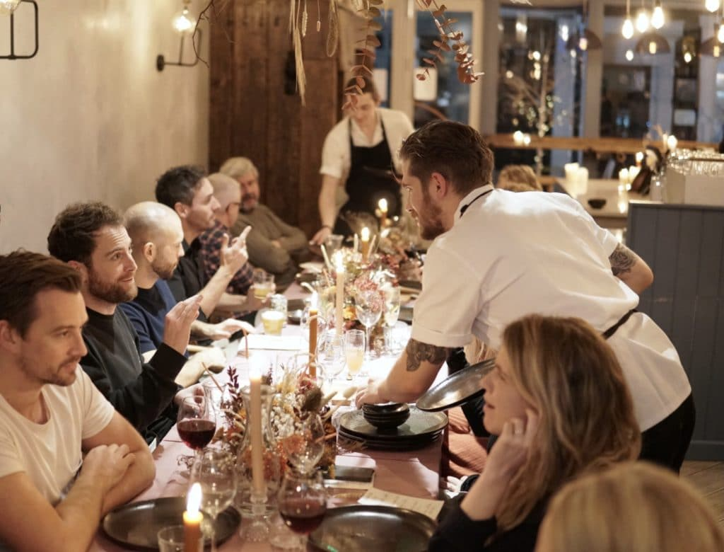 Guests at Lost Evenings at Lost in the Lanes Brighton, seated at a long table with chefs presenting them with dishes.