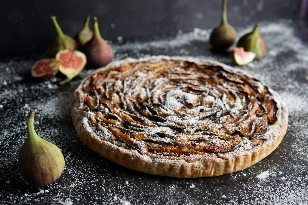 A caramel and fig tart on a grey surface dusted with icing sugar and figs arranged about it.