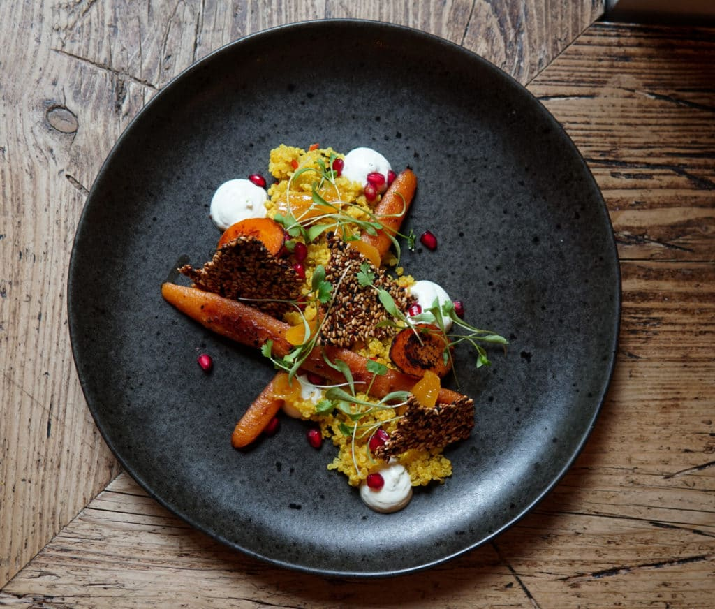 A gray plate on a wooden talbe on the plate is miso glazed carrot with sesame cracker, couscous, roasted tomato, pomegranate and micro-herbs