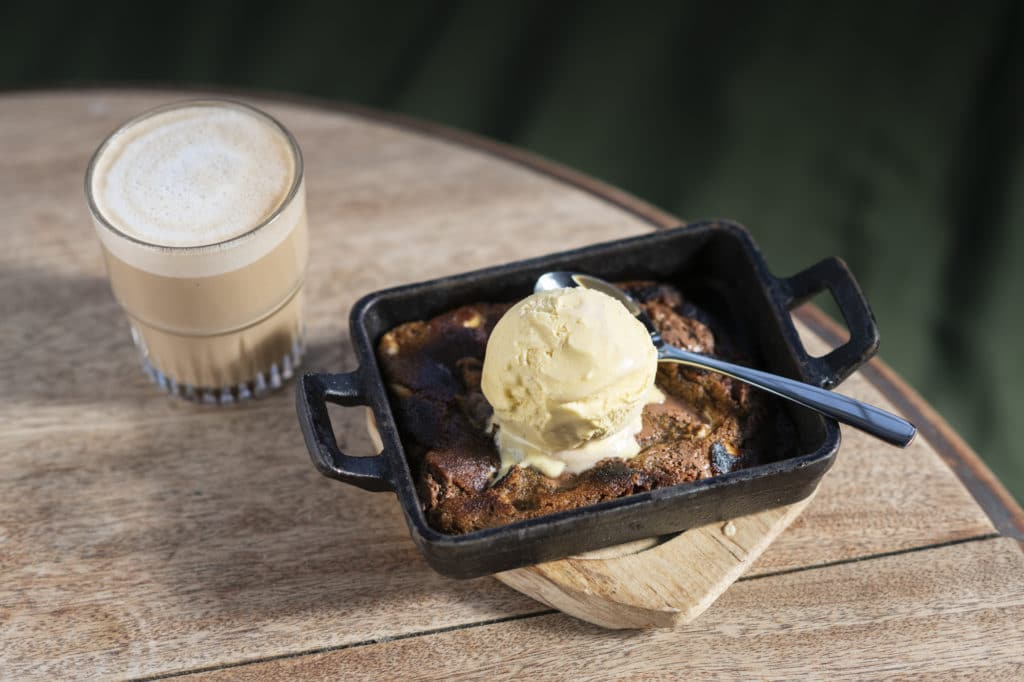 Baked cookie dough in a skillet with Gelato Gusto gelato and a latte served in a glass.