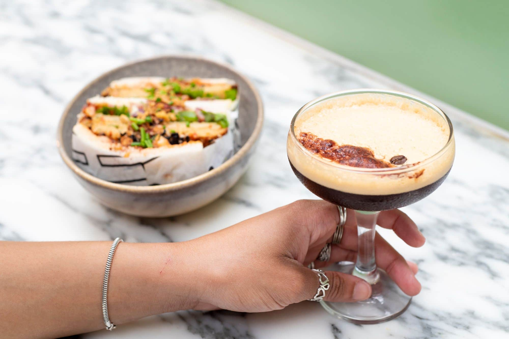 hand with rings on holding fancy glass of espresso martini