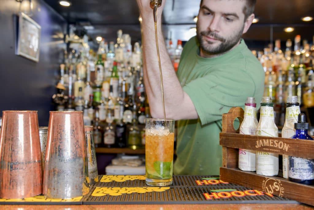 Bar man making cocktails