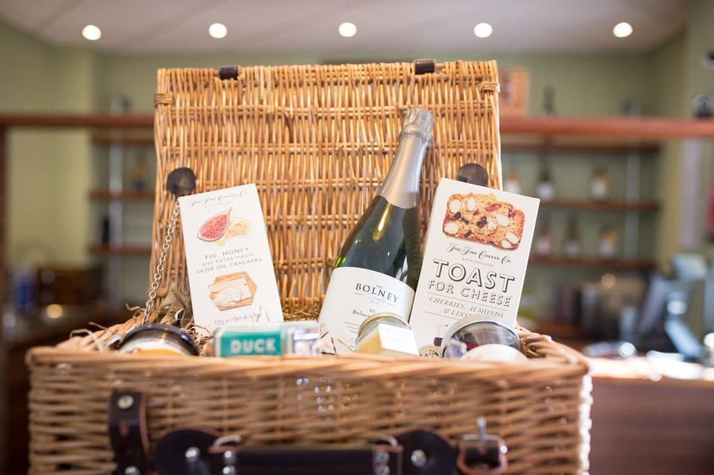 A wicker hamper basket filled with a selection of food items and wine