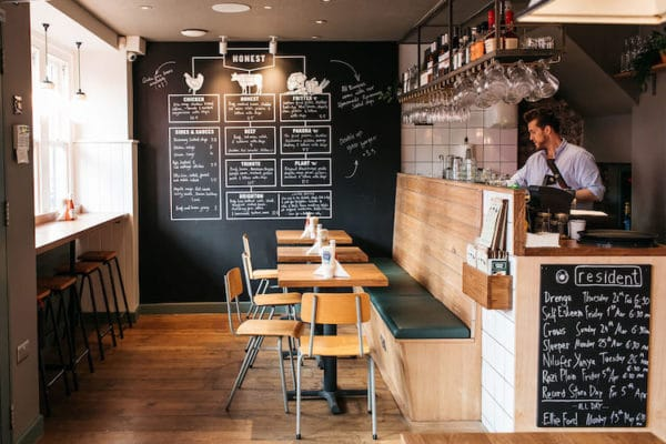 Interior shot of Honest Burger with tables lined up next to a black board menu on the wall.