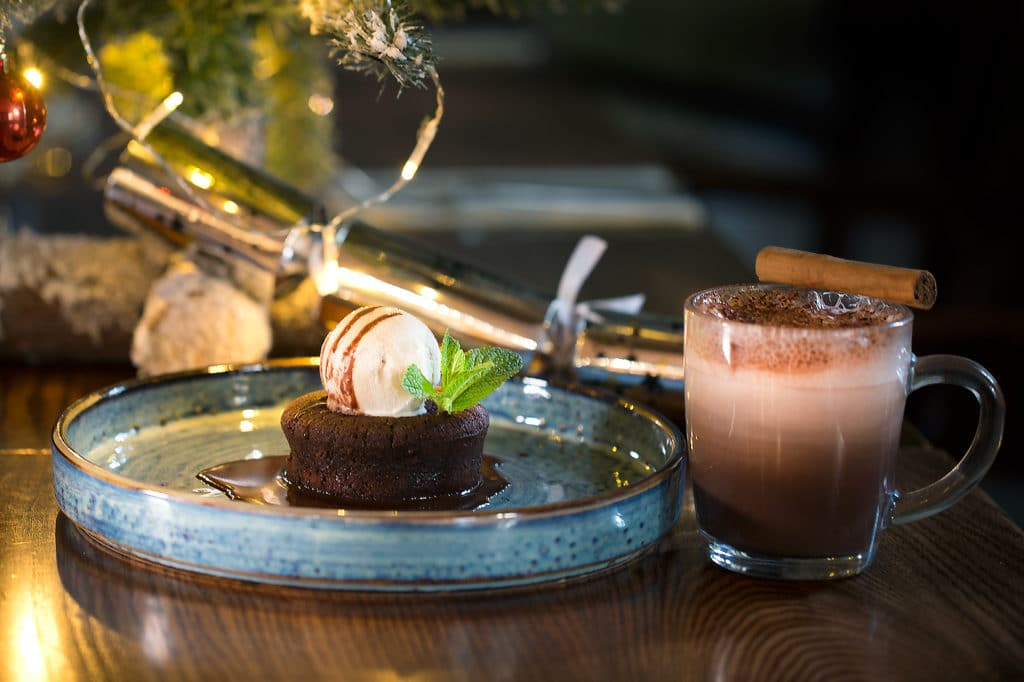 Hot chocolate pudding, chocolate sauce, a scoop of ice cream and a mug of frothy hot chocolate at Hove Place