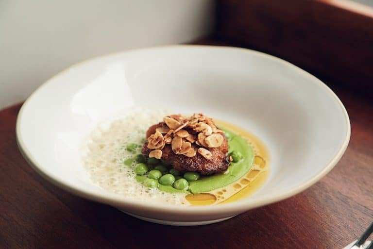 A large deep dish with a creamy pea puree topped with a piece of red meat and toasted flaked almonds