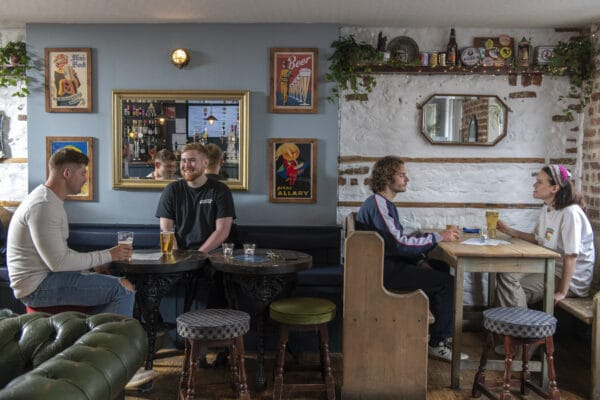 Freehaus interior showing different stools, table sizes, chesterfield sofa and people enjoying a drink