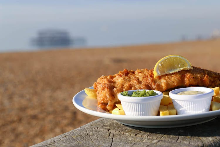 Fish & chips served with a wedge of lemon along with small pots of tartare sauce and mushy peas.