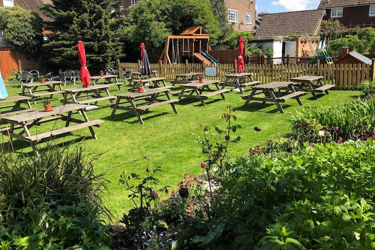 Traditional kitchen garden with a children's play area. Wooden benches lined up with parasols and plant pots.