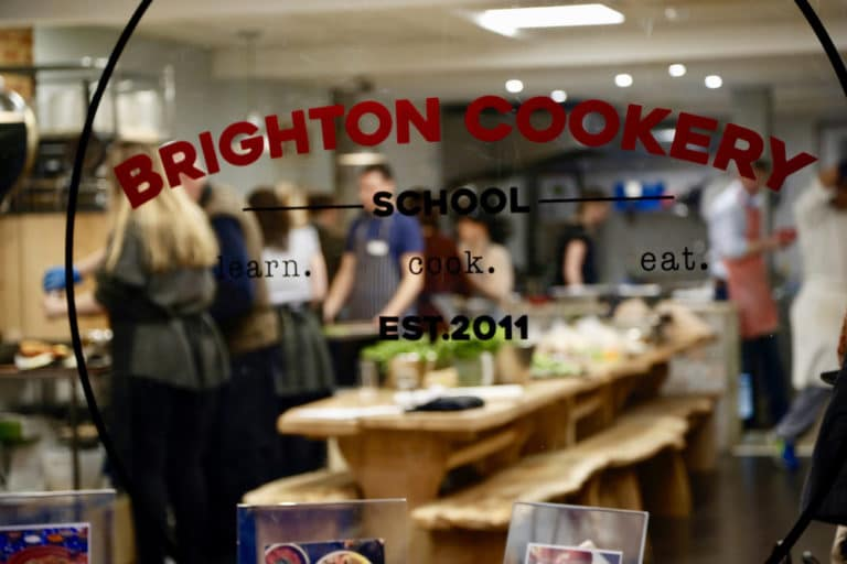 Looking through the window of the busy cookery school with people at a class