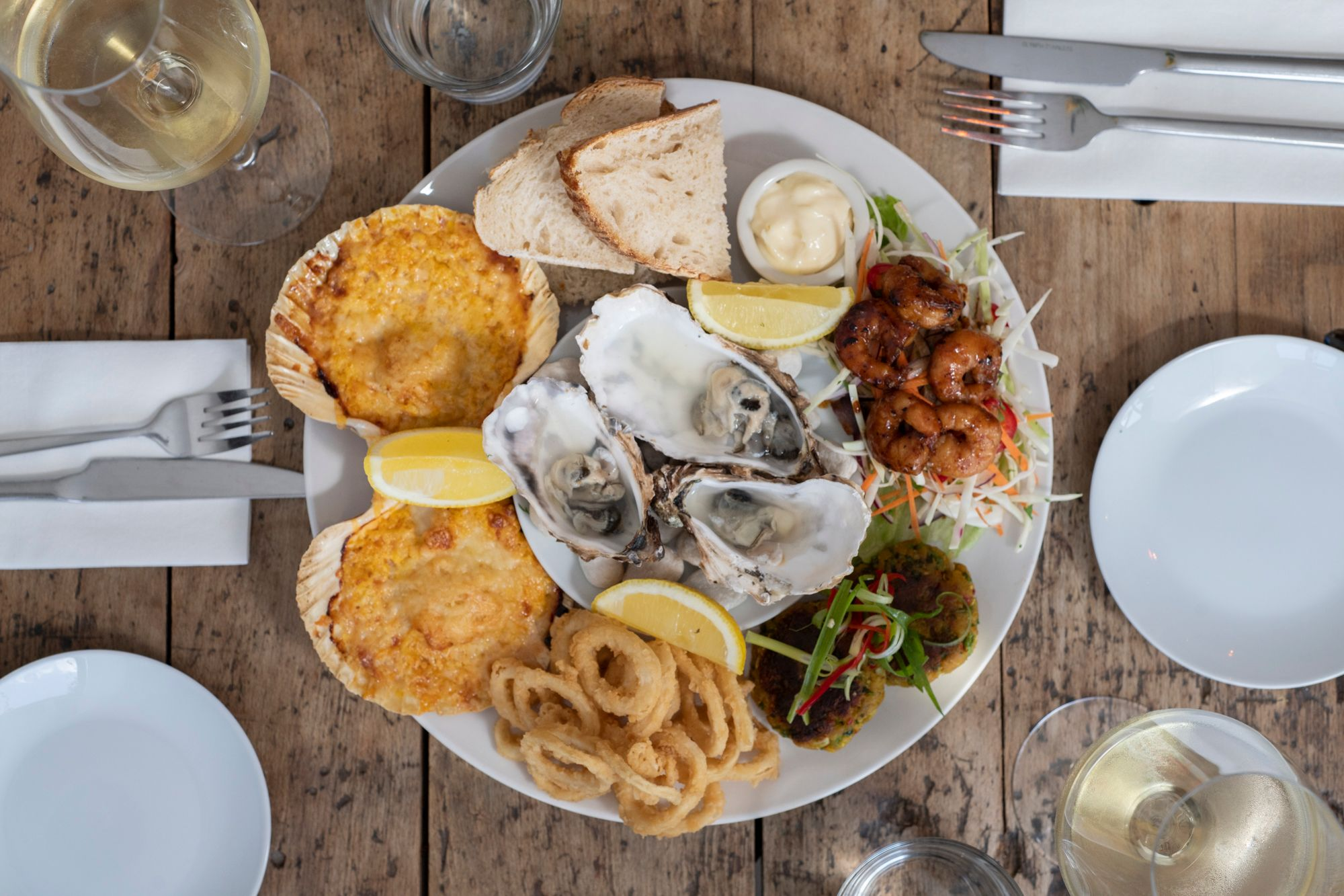table laid out with big plate with 3 Irish rock oysters on, onion rings, slice bread and white wine on the side