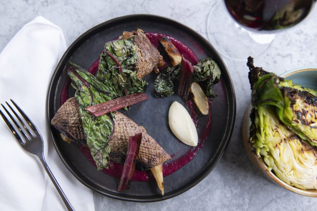 two dishes and a glass of wine at Kindling