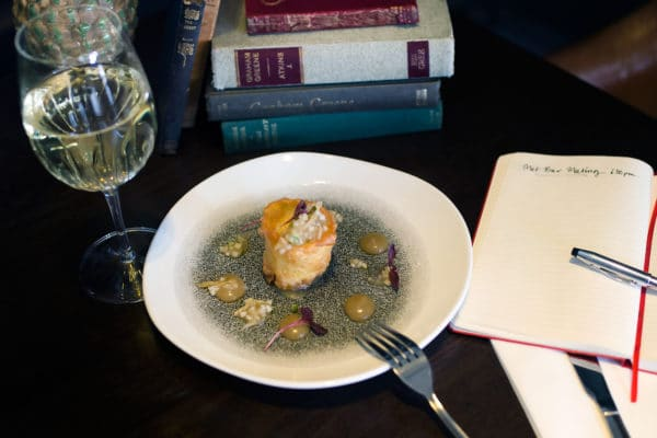 Dish of food, wine and notebook