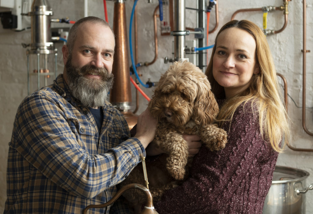 To the left a man in a plaid shirt, he has a thick beard and handlebar moustache, to the right there is a strawberry blond haired woman in a mauve jumper. They are holding a brown dog between them, in the background there are lots of pipes