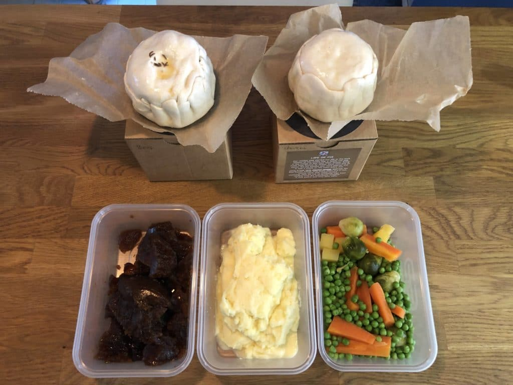 two uncooked pies on top of brown kraft boxes and three containers of vegetables, mashed potato and onion gravy laid out on a wooden table