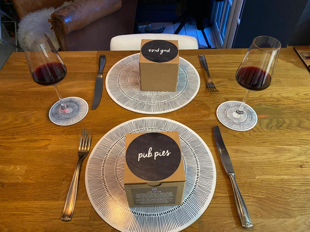 """two boxes on plates at a dining table set for two with two glasses of wine. The brown boxes have black round labels on them that read """"pub pies"""""""