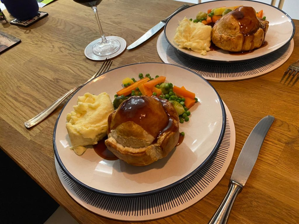 two plates of handmade pie served with mash and mixed vegetables
