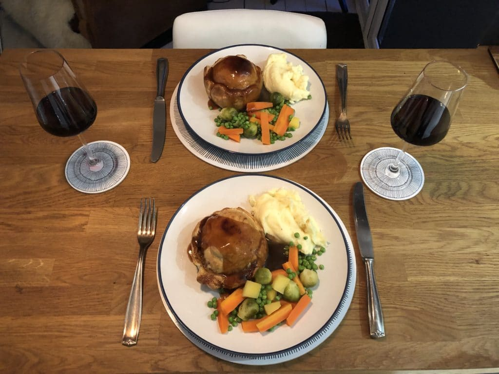 overhead shot of two plates of homemade pies with mash, mixed veg and onion gravy