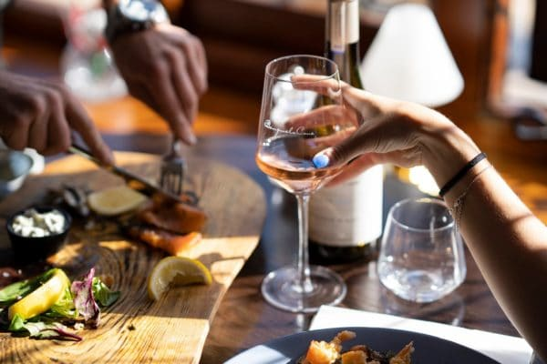 A hand holding a glass of rosé wine is opposite a pair of hands with cutlery taking food from a charcuterie board.