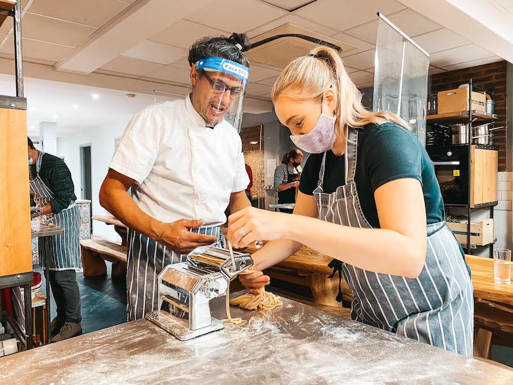 Messa Ben talking a student through using a pasta making machine to feed through tagliatelle