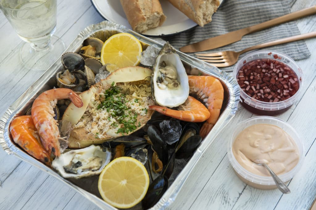 Fresh seafood platter with dipping sauces and crusty bread.