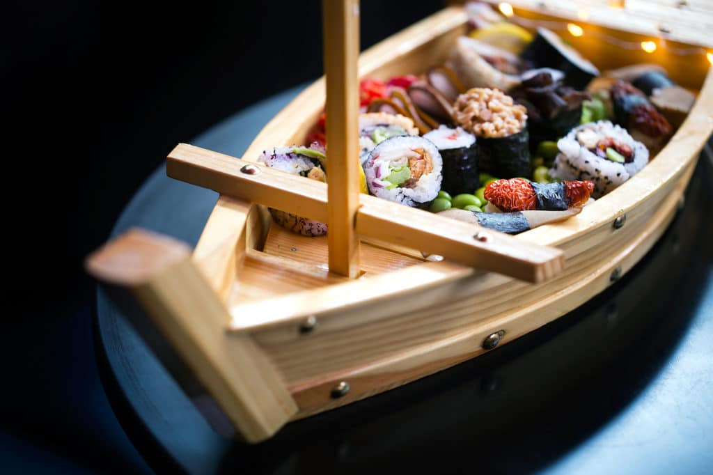 A bamboo boat filled with sushi on a dark shiny table