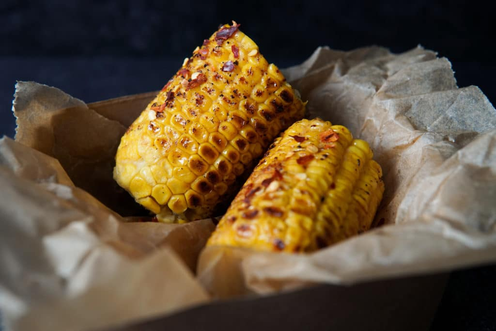 two corn on the cobs, slightly charred and glistening with miso butter, available from Tide Brighton