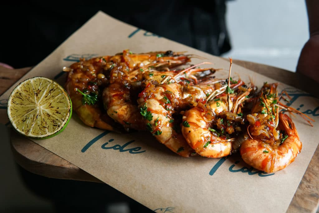 Rum tiger prawns with a burnt lime half, served on a wooden board with a piece of parchemnt on it and the word Tide in blue written on it.