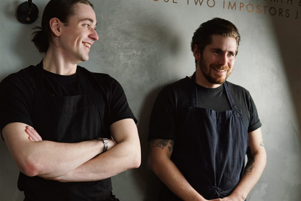 The Tide team, Chefs James and Raph. Raf to the left is earing a balck t-shirt and is looking over his left sholder at James. James, also in a black t-shirt and navy apron holds his hands in his lap and smiles while looking forward.