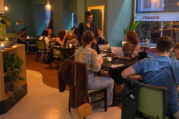 interior of Longrain Thai Brighton, tables of two or four diners are being served in the restaurant that has large windows, light wooden floors and deep green walls.