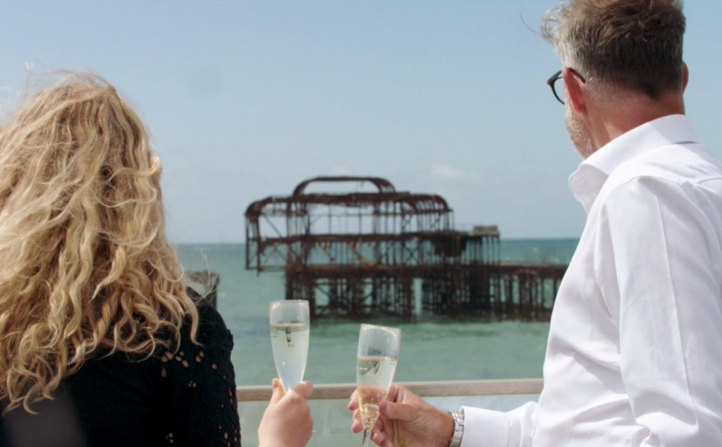 A couple drinking champagne looking out at the Brighton West Pier