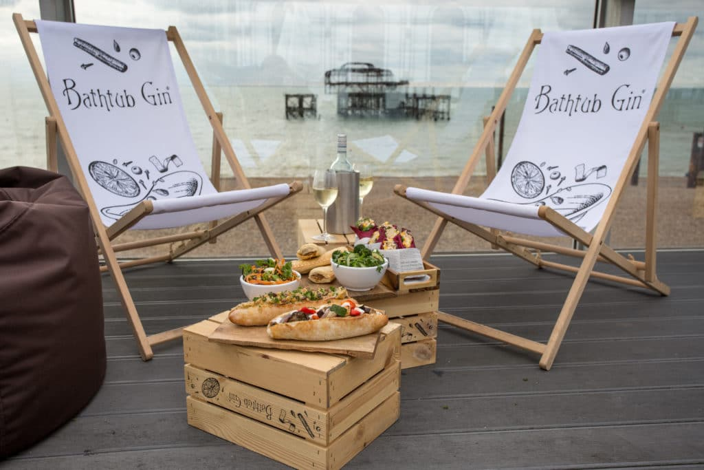 two deckchairs and two low tables with cafe style sandwiches and paninis, in the background is the Brighton West Pier