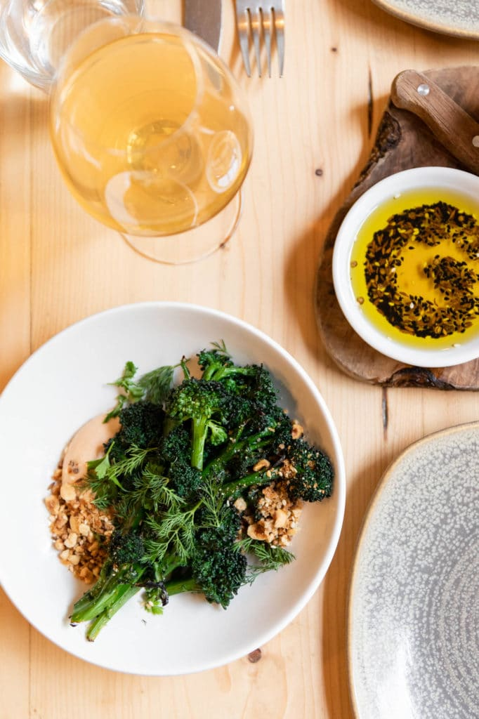 On overhead shot of a wooden table with a dish of broccoli, a vinaigrette and a glass of orange wine