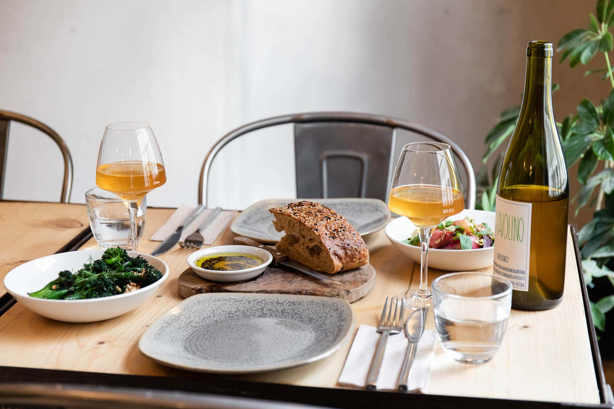 a wooden table and metal chair laid with two grey plates two glasses of orange wine and a selection of small plates