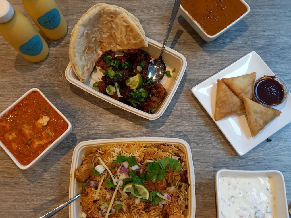 Overhad shot of an Indian takeaway with byriani, black dahl, paneer and samosas